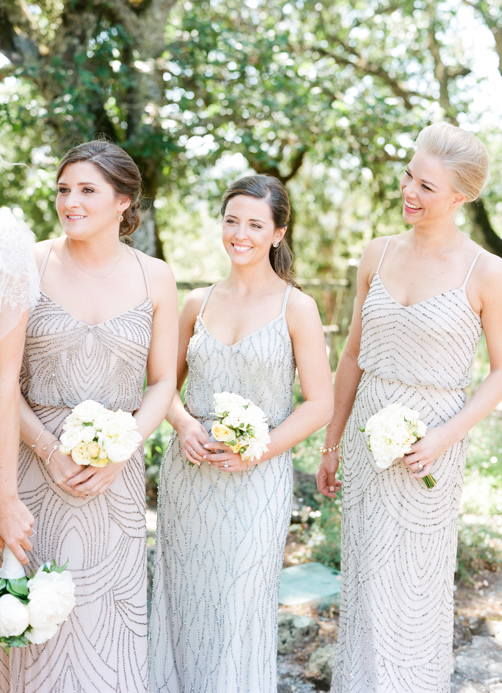 The bridesmaids, dressed in loose, sequined gowns smile toward the bride on her wedding day, holding white bouquets; photo by Sylvie Gil