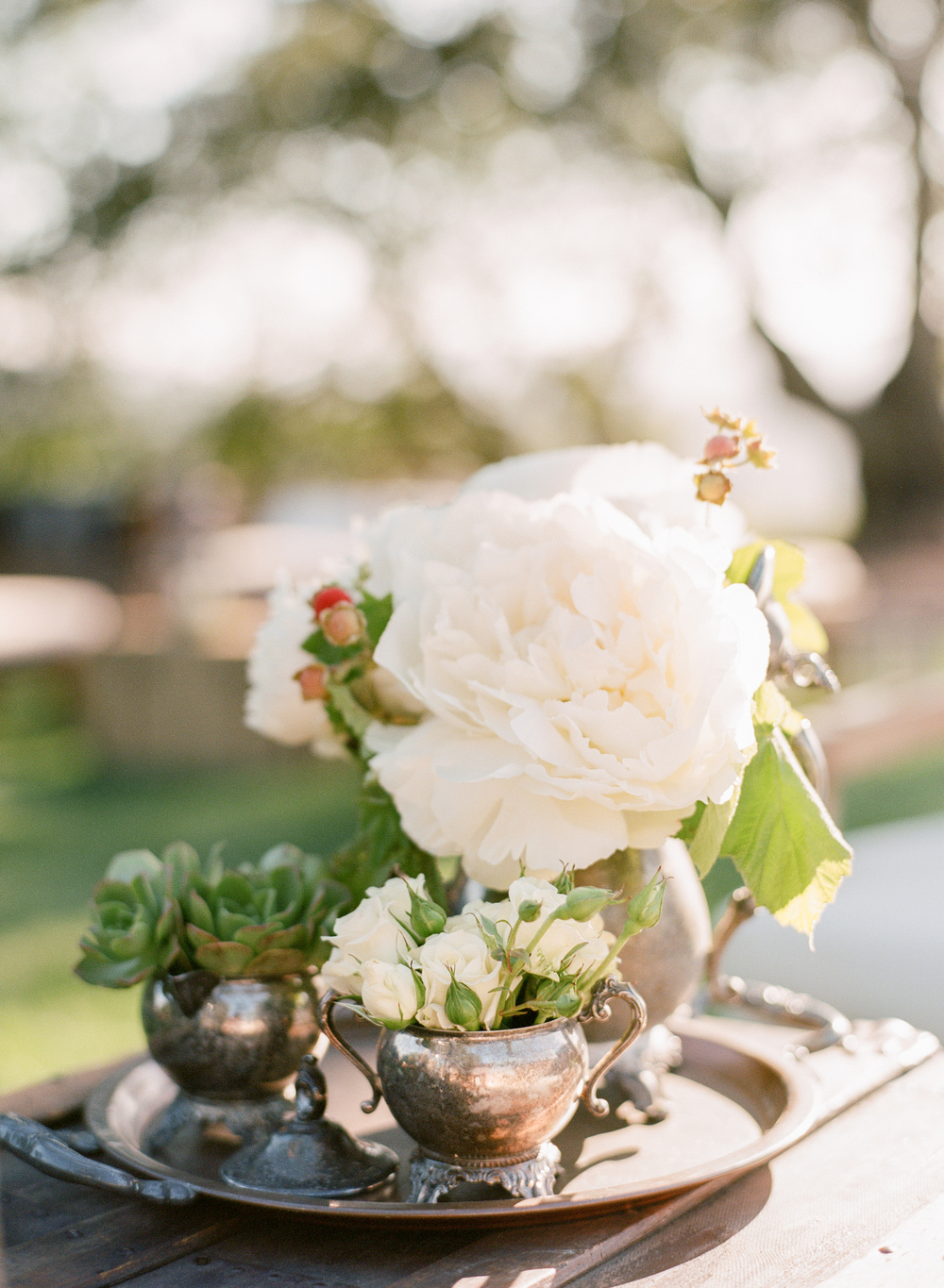 Peonies and succulents arranged in tarnished antique vases set on a tray in the reception; photo by Sylvie Gil