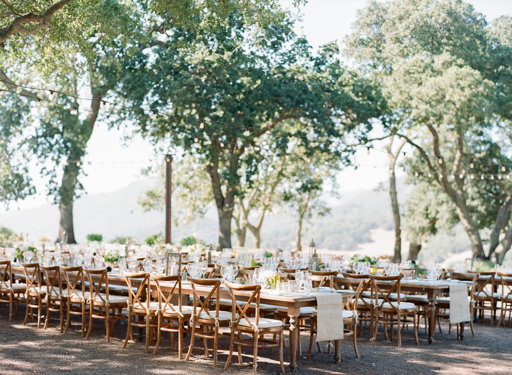 String lights sweep over the long wooden reception tables for a very romantic atmosphere; photo by Sylvie Gil