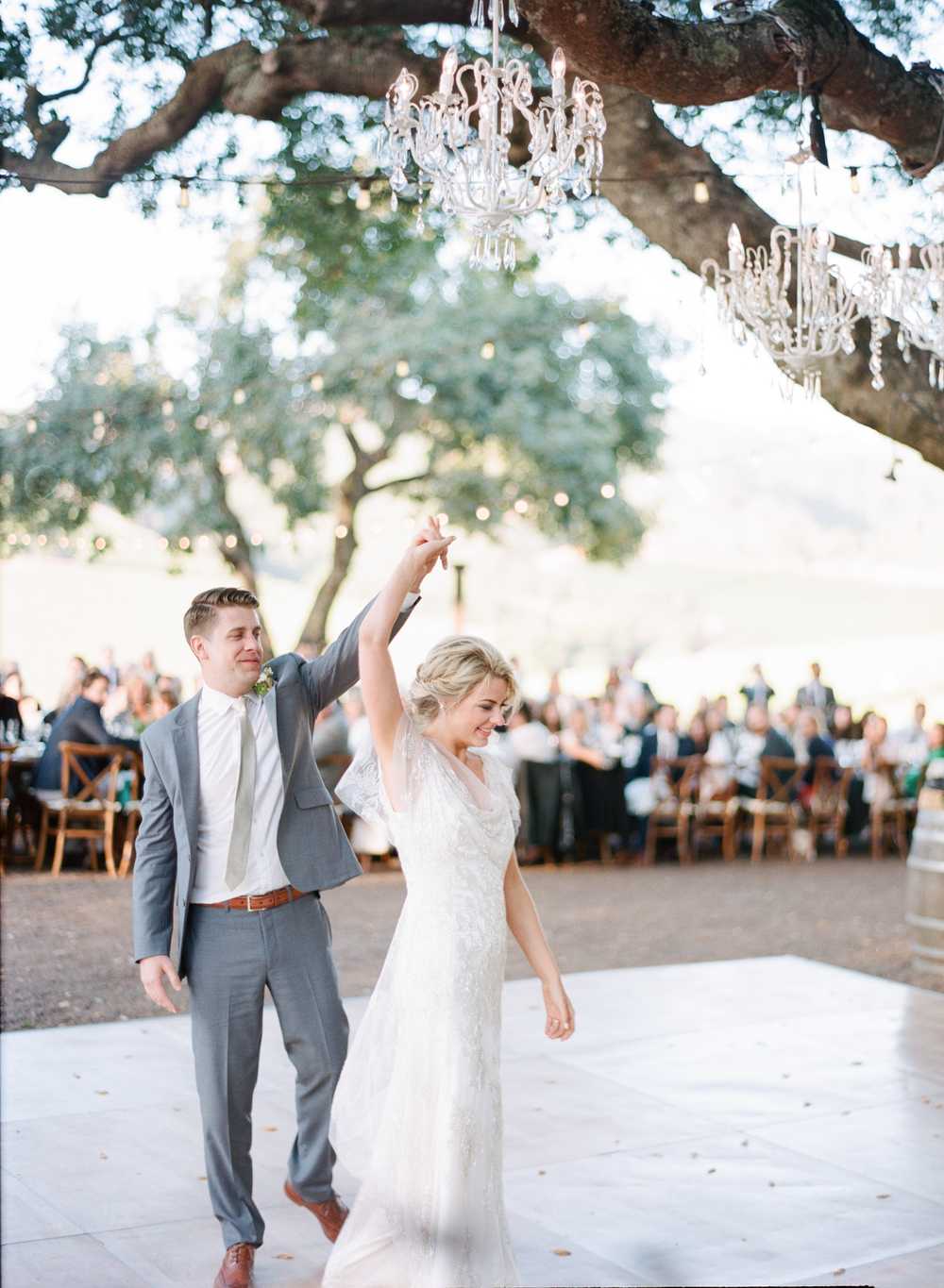 Chandeliers hang from the oaks over the dance floor as the couple takes their first dance; photo by Sylvie Gil
