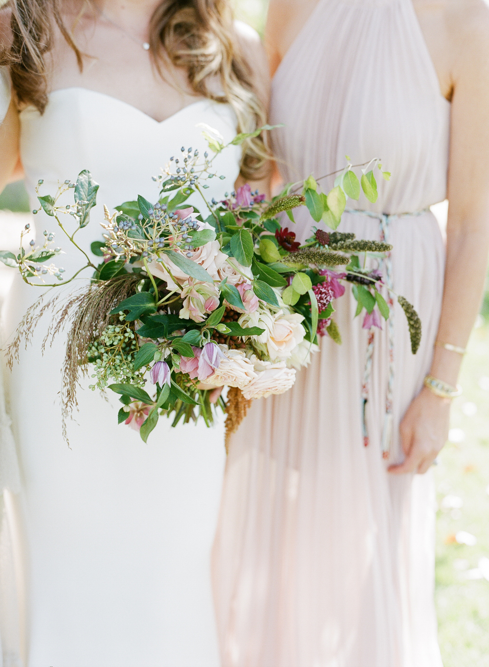 Tali, with a gorgeous, eclectic bouquet spilling out of her hands, stands with her bridesmaid; photo by Sylvie Gil