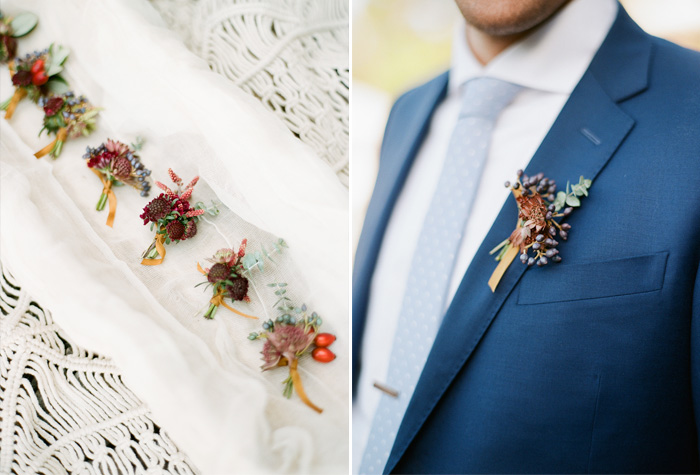 The colorful, earthy boutonnieres sit on a macrame sheet, the groom wears his on his navy suit; photo by Sylvie Gil
