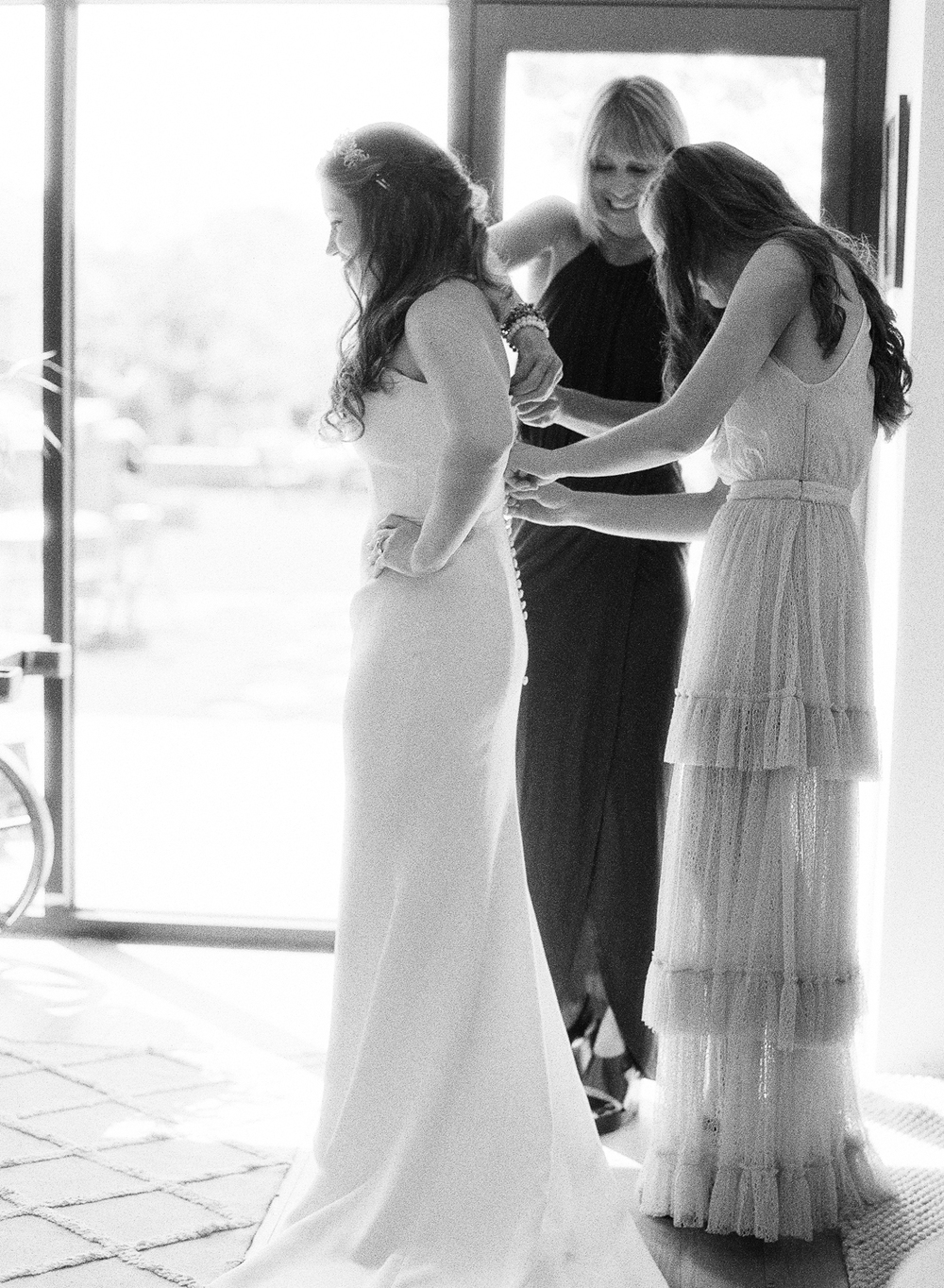 Tali's sister and mother lace up her simple, yet beautiful gown before the wedding; photo by Sylvie Gil