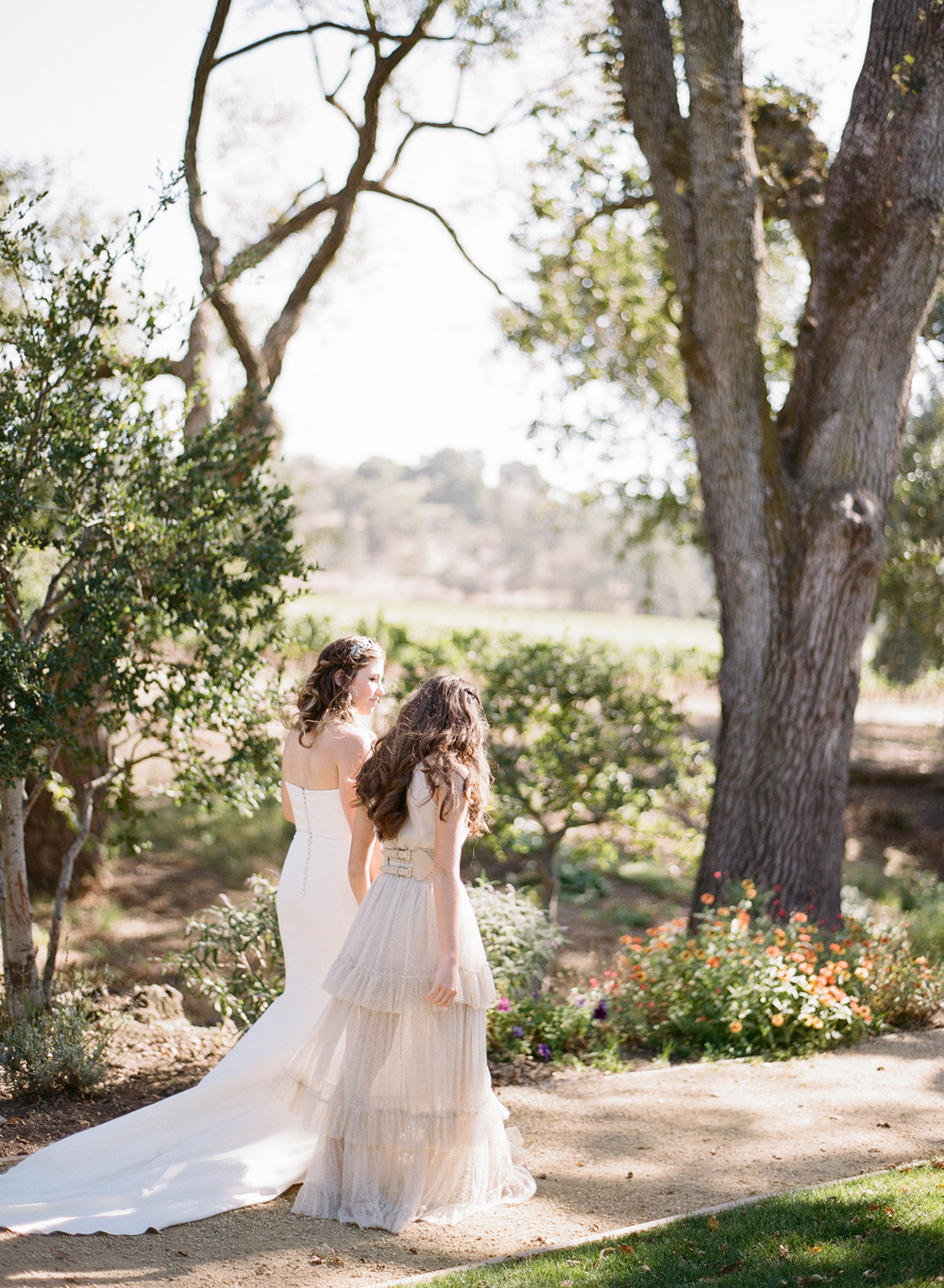 Tali and her sister, dressed in a tiered chiffon gown, walk towards the ceremony space; photo by Sylvie Gil