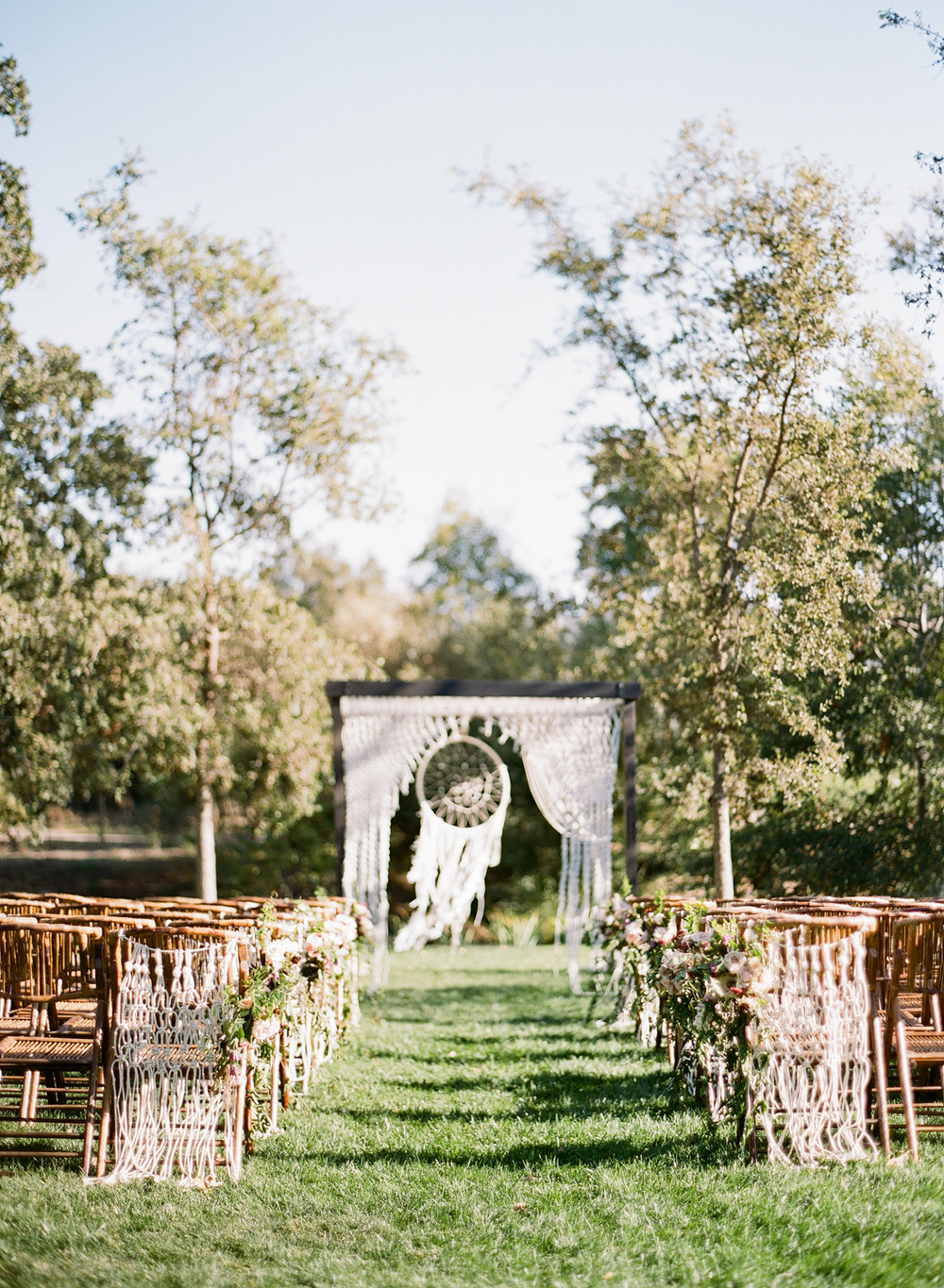 The ceremony space is framed by a giant macrame dream catcher, crafted by the bride herself; photo by Sylvie Gil