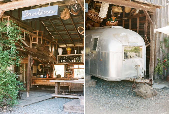 The interior of a rustic barn near the reception; a Cantina sign hangs next to an old fashioned camper; photo by Sylvie Gil
