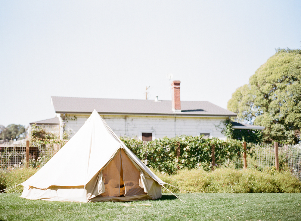 A tent pitched in a nearby field adds to the bohemian feeling of the wedding; photo by Sylvie Gil