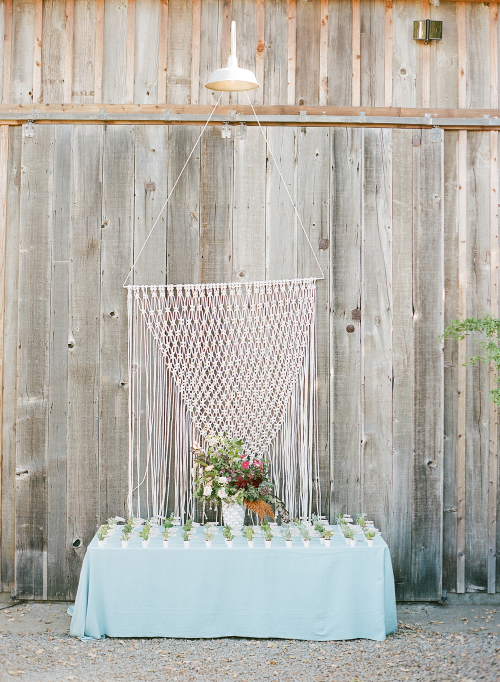 A handmade macrame backdrop hangs behind the place card table; photo by Sylvie Gil