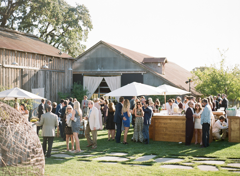 Guests mingle in the garden outside the barn before the reception; photo by Sylvie Gil