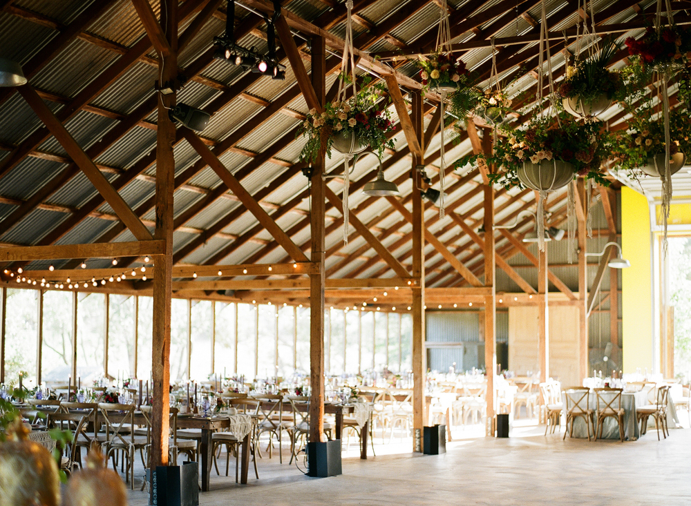 Afternoon light floods the barn for the reception, hung with baskets of flowers and string lights; photo by Sylvie Gil