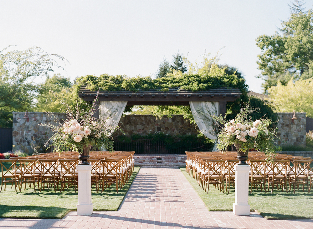The intimate ceremony space is marked by two sprawling floral accents, consistent with the blush-and-cream color palette; photo by Sylvie Gil