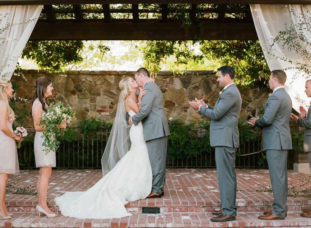 "A romantic kiss after the couple has said ""I do"" during their Napa ceremony; photo by Sylvie Gil"