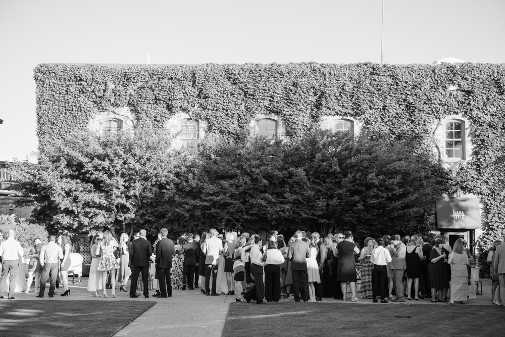 The exterior of a vine-covered building in the winery, guests mingle and enjoy cocktails before the outdoor reception; photo by Sylvie Gil