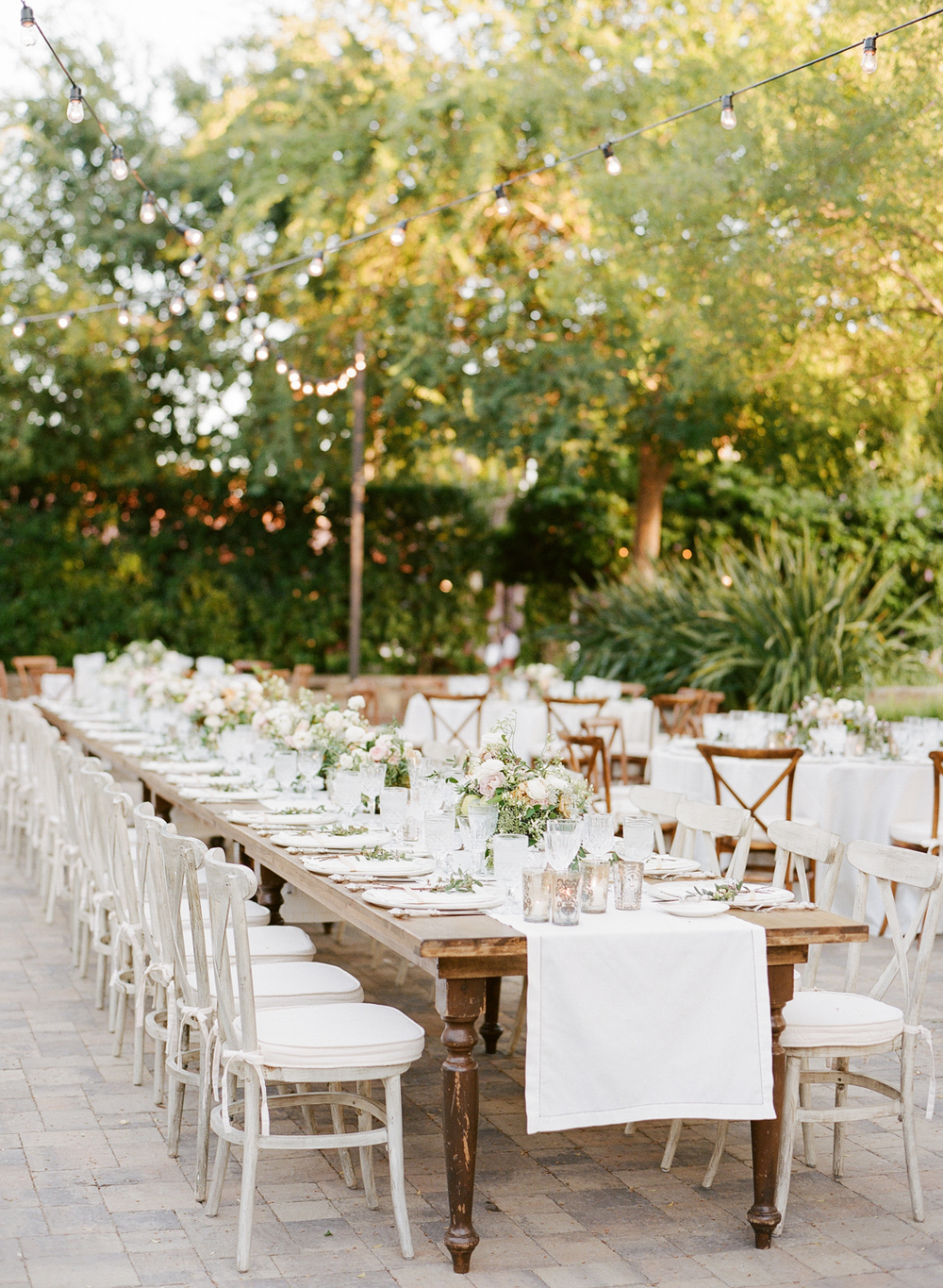 Rustic wooden tables lined with crisp white linen runners create a fresh spring look to this outdoor reception; photo by Sylvie Gil