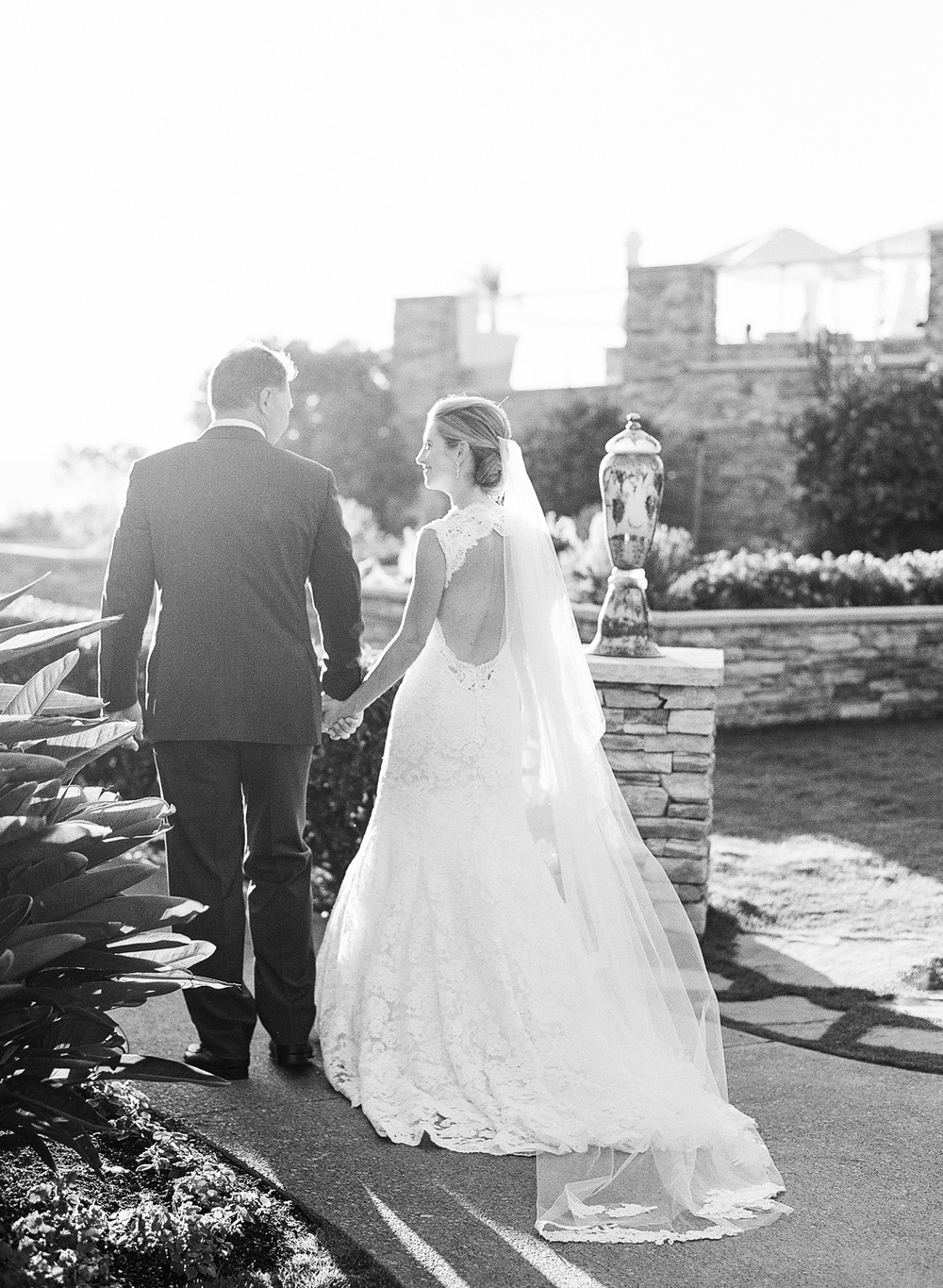 Newly married, Margo & Tanguy walk toward their outdoor, beach reception at the Ritz Carlton in Laguna Beach; photo by Sylvie Gil
