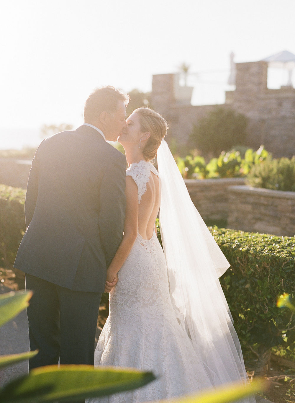 Newlyweds pause for a kiss in the sunset, just before their Laguna Beach reception; photo by Sylvie Gil