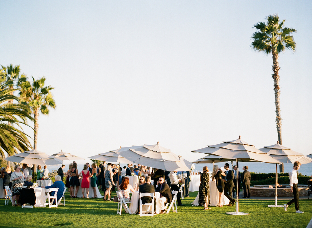 Guests mingle for cocktails during the outdoor reception, enjoying the Southern California sun; photo by Sylvie Gil