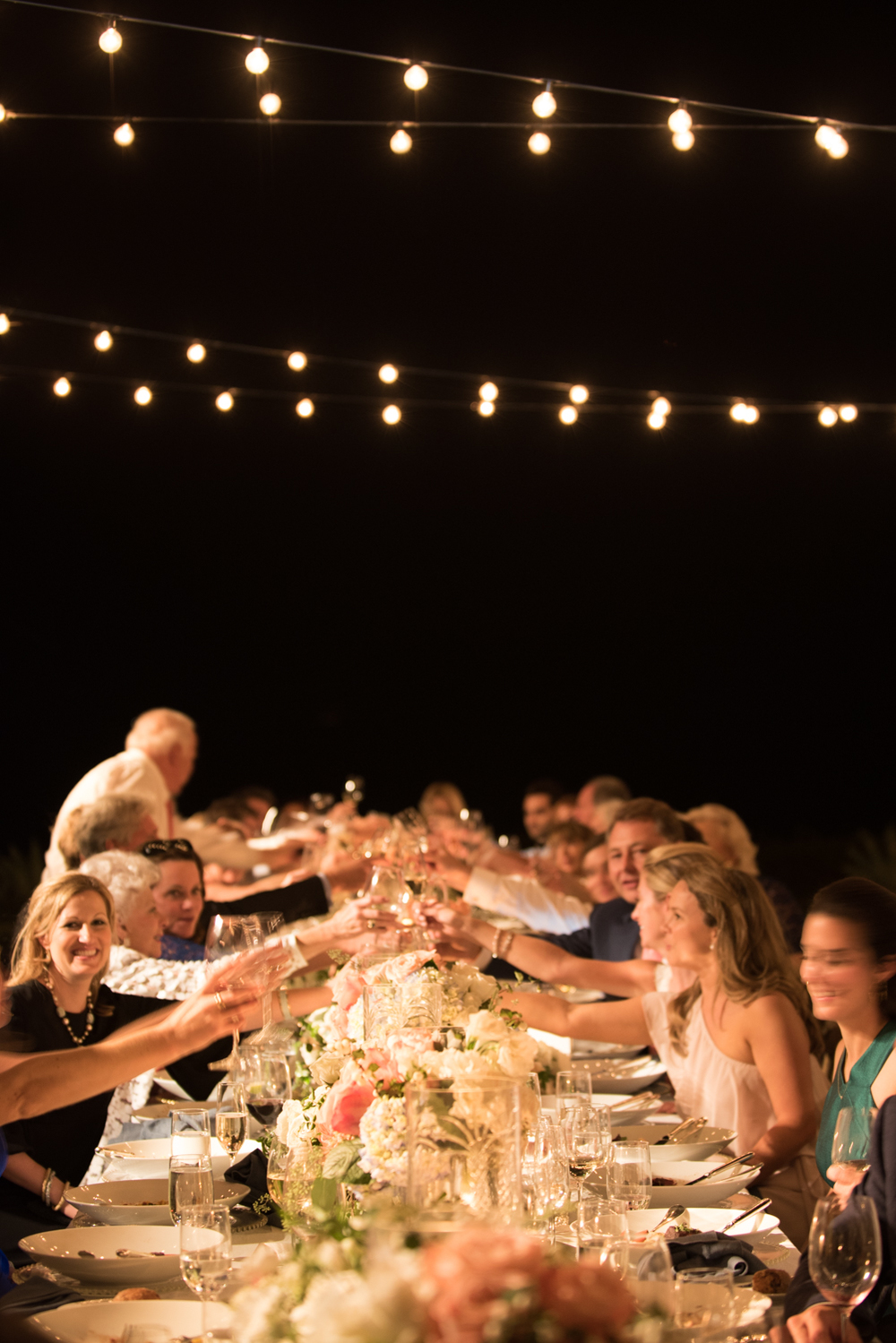 Guests toast as night falls over the gorgeously laid reception tables lit by string lights; photo by Sylvie Gil