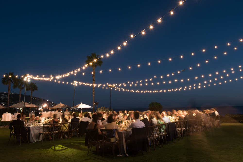 String lights provide a romantic atmosphere for the outdoor Laguna Beach reception; photo by Sylvie Gil