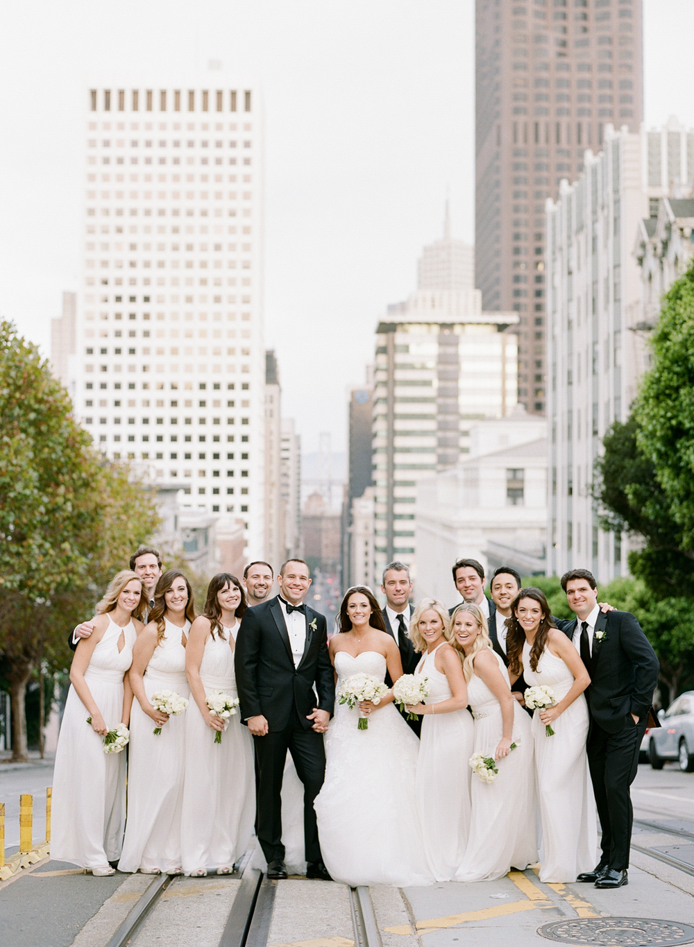 Meg, Ben, and their bridal party pose in the middle of a San Francisco street (on streetcar tracks, no less); photo by Sylvie Gil