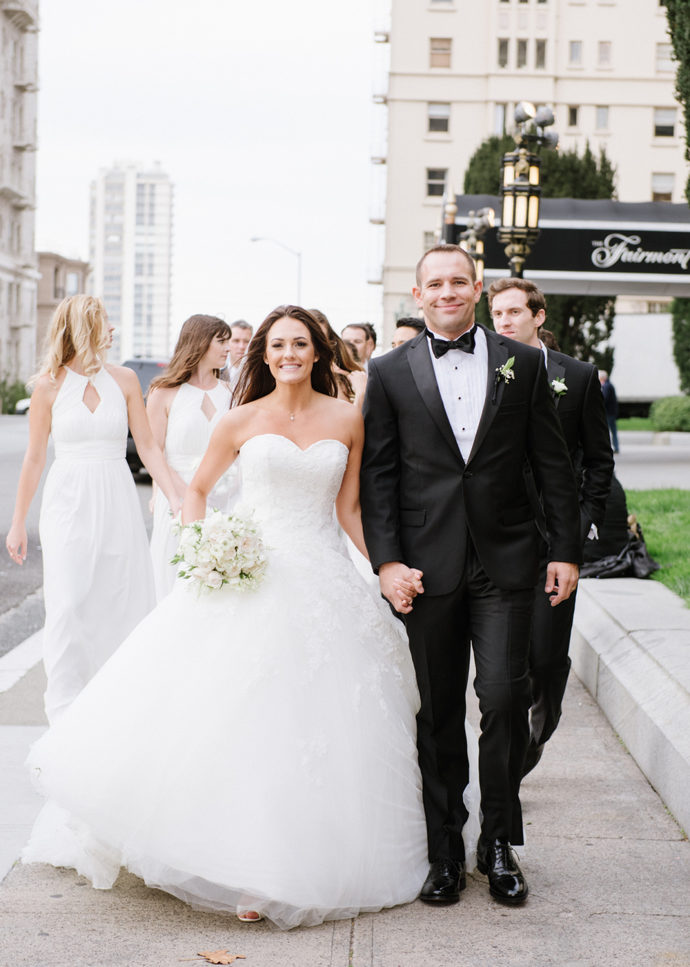 Newlyweds walk down a San Francisco sidewalk toward the camera during a couple shoot; photo by Sylvie Gil