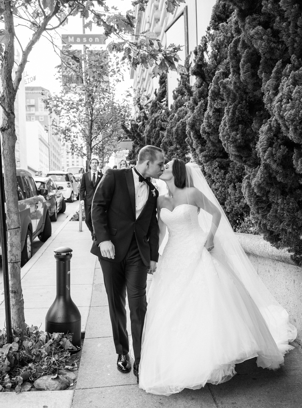 Leading their groomsmen and bridesmaids, Meg & Ben walk down a San Francisco sidewalk toward the camera; photo by Sylvie Gil