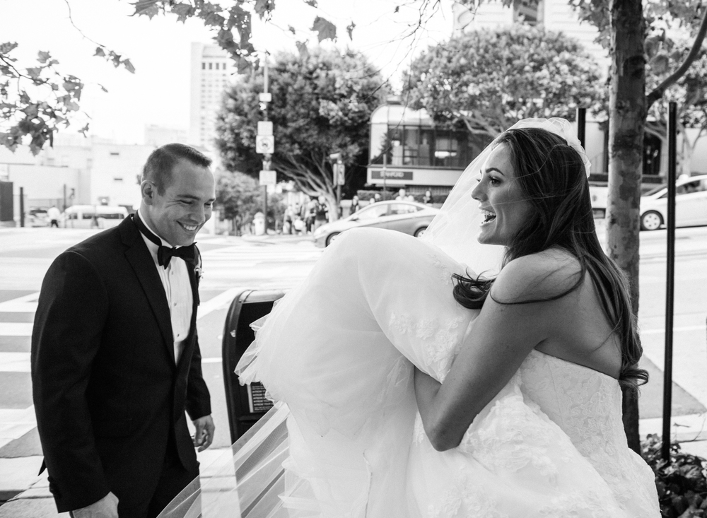 A beautiful candid photograph of the bride and groom walking through San Francisco after their rooftop wedding at the Fairmont Hotel; photo by Sylvie Gil