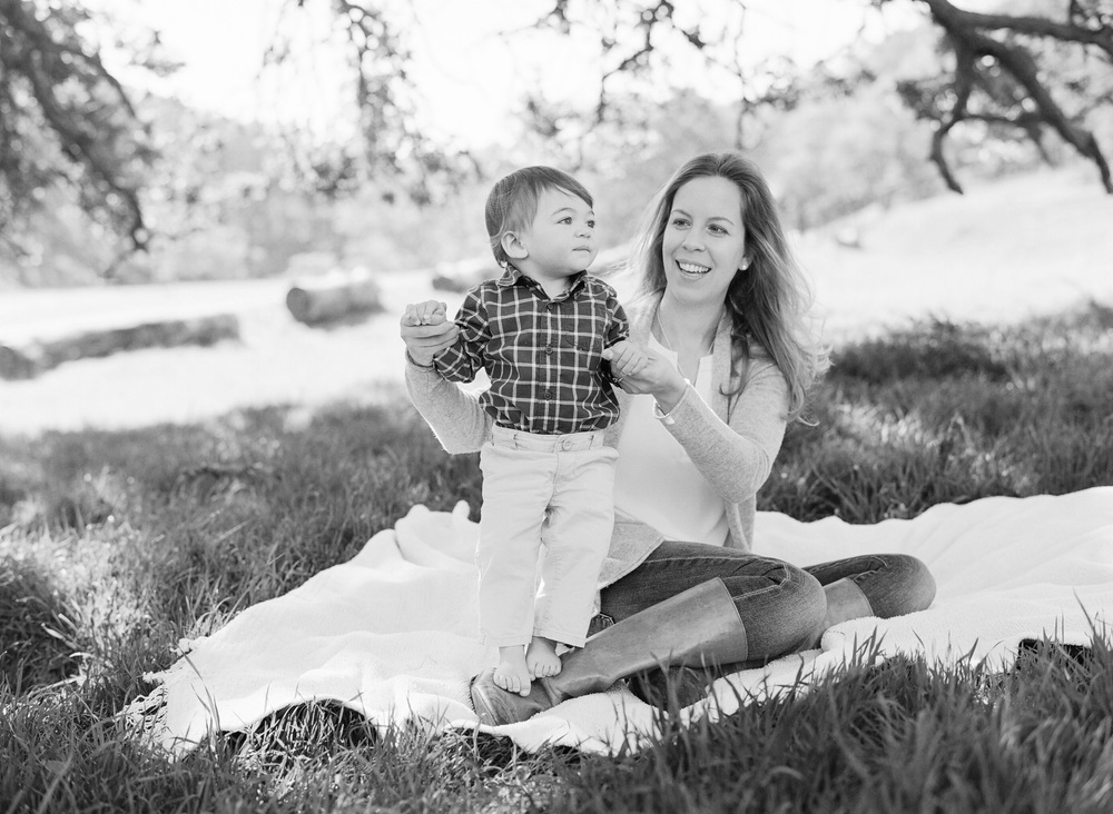 Baby boy stands, balancing in his mother's arms on a picnic blanket in the countryside during a family photoshoot with Sylvie Gil