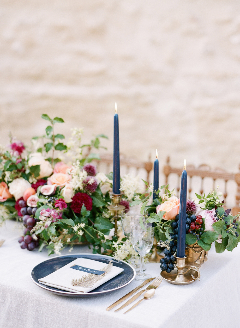 Navy and gold table settings, reception table with fruit and floral centerpieces; Sylvie Gil Photography