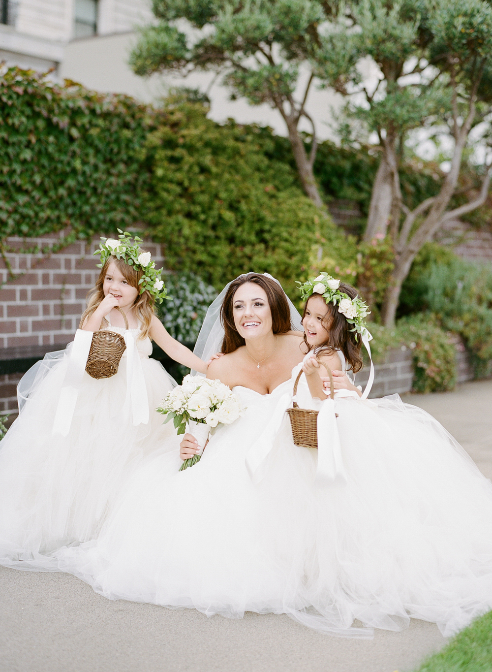 The bride poses with two flower girls in flower crowns; Sylvie Gil Photography