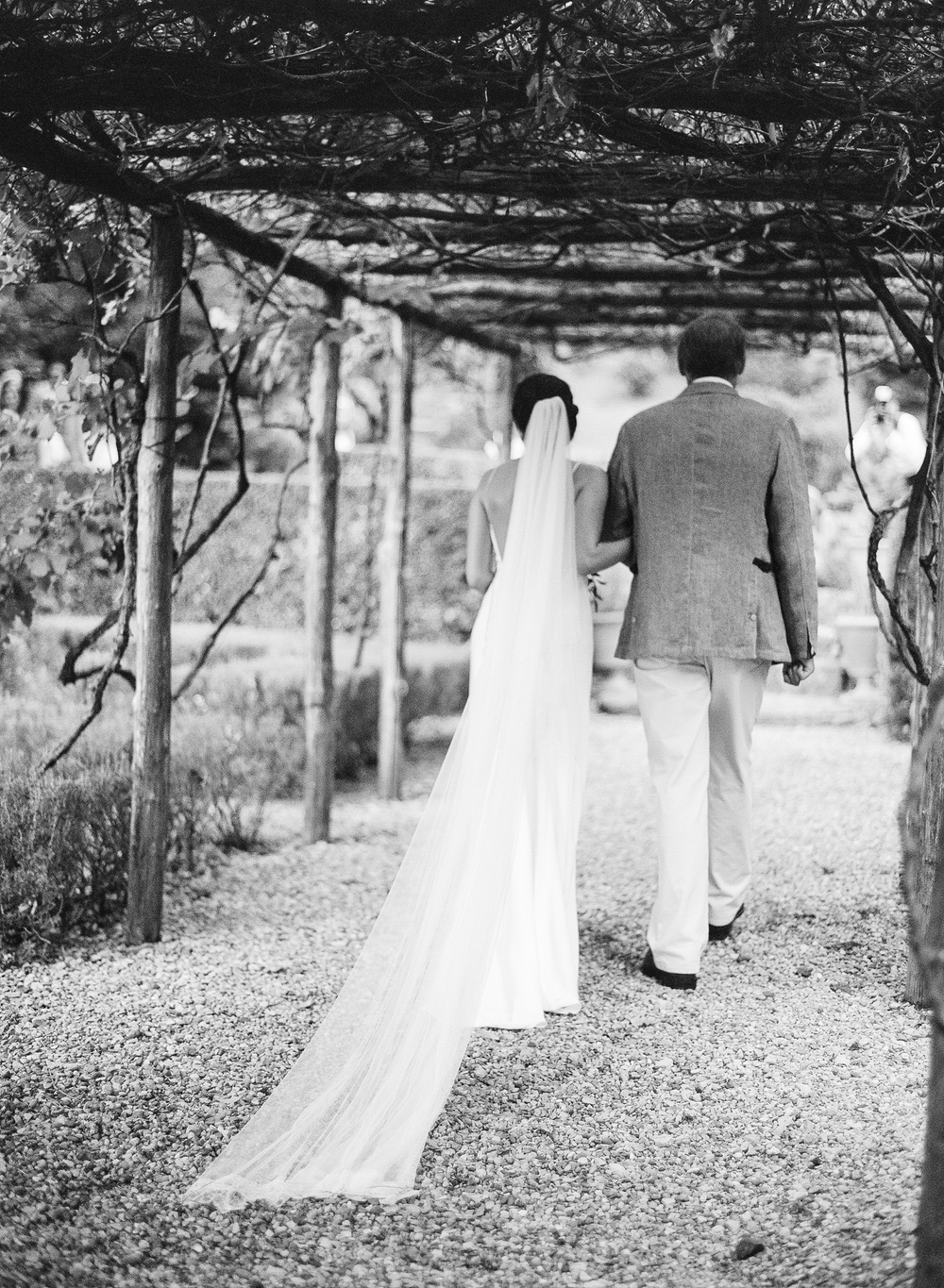 Amelie and her father walk up a gravel path to the chapel, arm in arm; photo by Sylvie Gil
