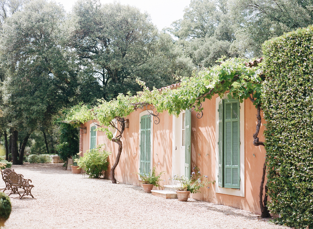 A salmon-painted cottage on the estate draped with vines and hanging green grapes; photo by Sylvie Gil