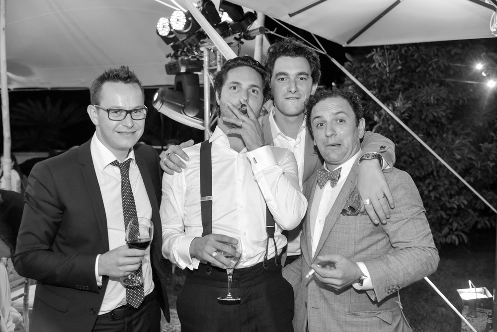 Laurent, the groom, smokes a cigar with three friends at the outdoor reception on an estate in Provence, France
