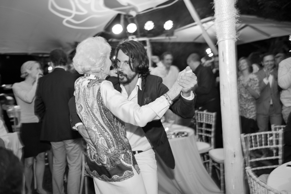 A young man dances with an old woman at the outdoor reception; photo by Sylvie Gil