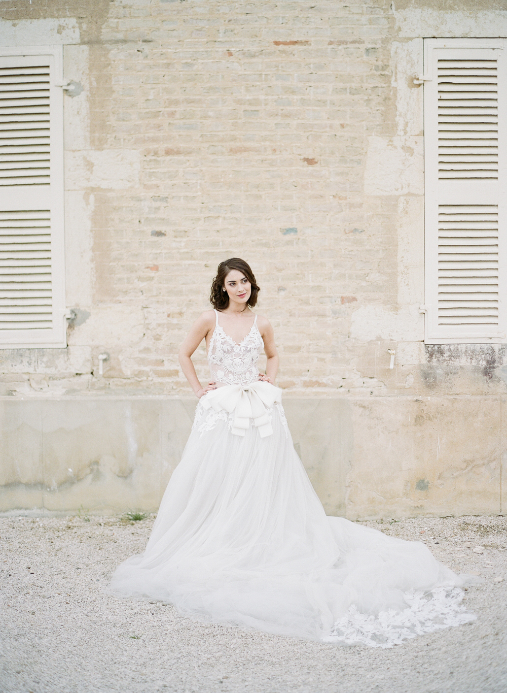 The bride poses in a dreamy Vera Wang gown in front of the chateau; photo by Sylvie Gil