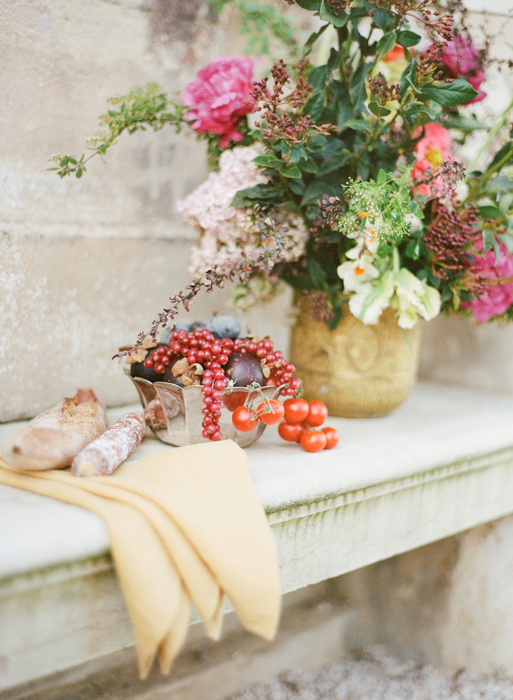 Charcuterie, a baguette, a bowl of fruit, and some lovely rustic florals make for a beautifully style detail shot from the 2016 Workshop in Burgundy; photo by Sylvie Gil
