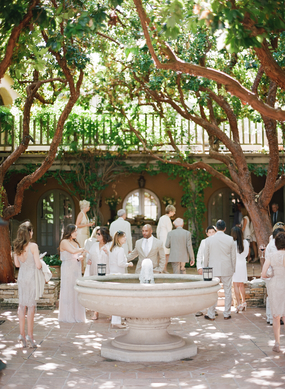 Guests and members of the bridal party mill around a fountain in the courtyard of the wedding venue, dressed in cream, white, and beige; photos by Sylvie Gil