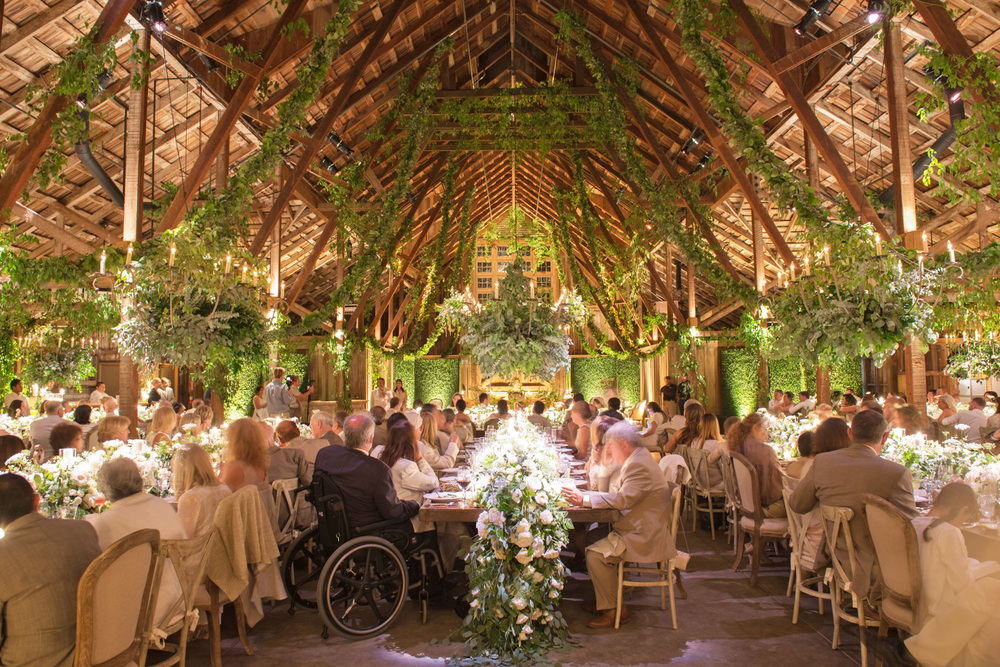 Guests listen to toasts of the bride and groom at the barn reception, the barn is strewn with florals and vines for a forest-like atmosphere; photo by Sylvie Gil