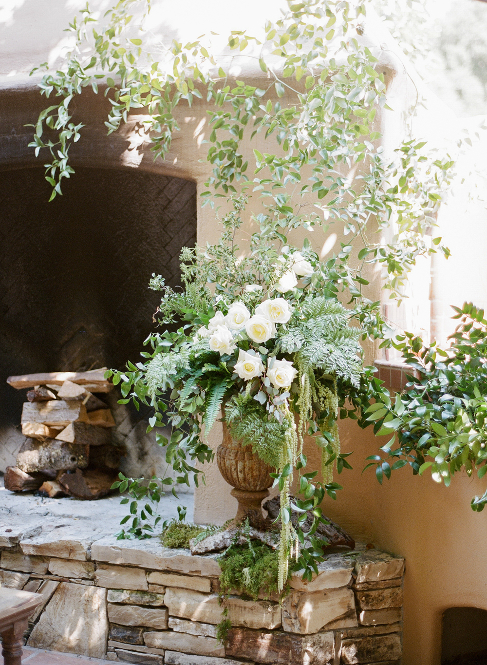A terra cotta vase spills over with ferns, moss foliage, and white roses next to a fireplace in the reception courtyard; photo by Sylvie Gil