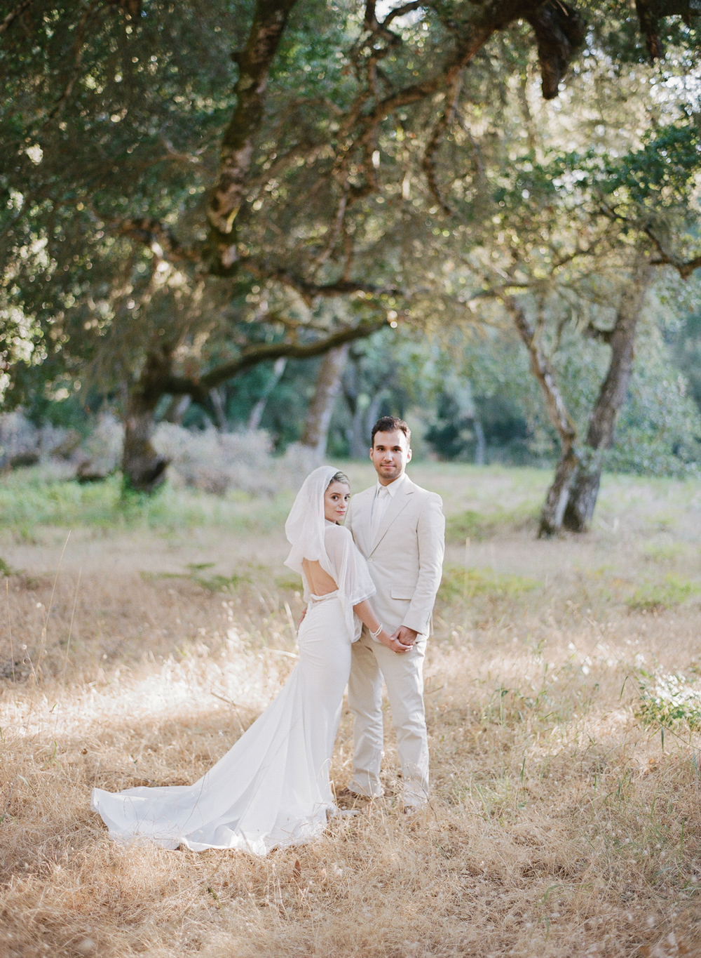 The bride and groom stand among old oaks in Santa Lucia; photo by Sylvie Gil