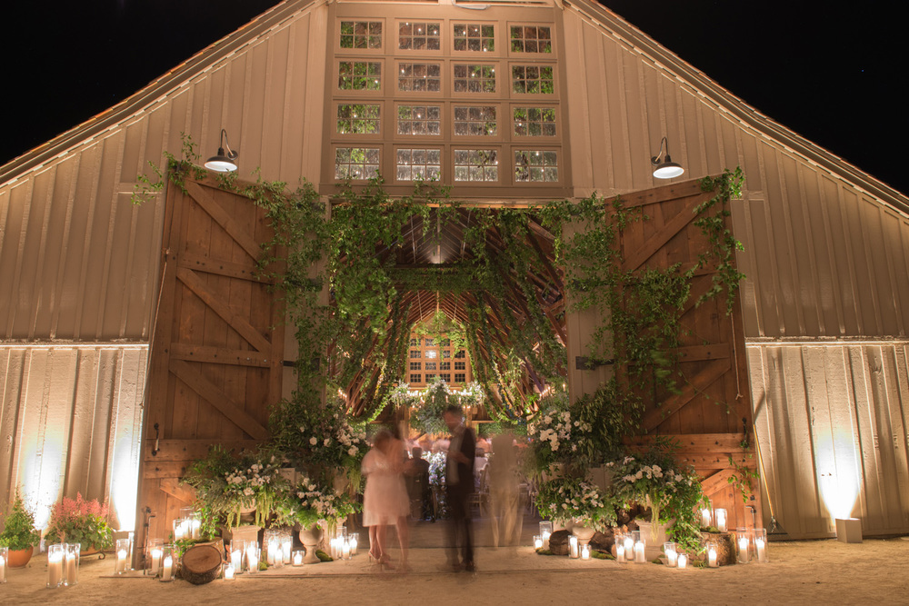 Guests mingle inside and outside of the rustic, intricately decorated barn during the reception; thick green vines hang from the rafters and climb over the wide, candle-lined wooden doors; photo by Sylvie Gil