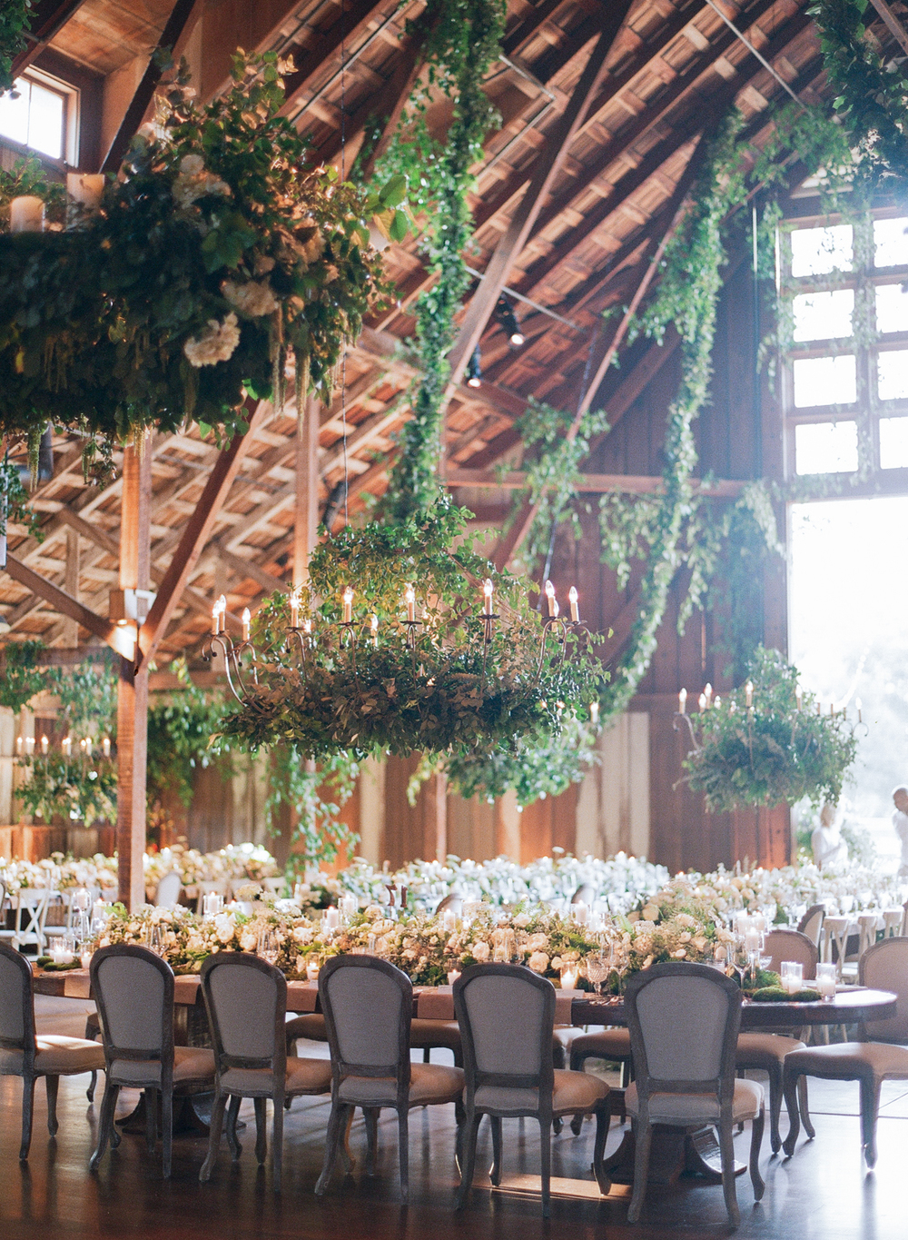 A chandelier lined with thick vines and ferns hangs over a reception table with a wide floral table runner; photo by Sylvie Gil