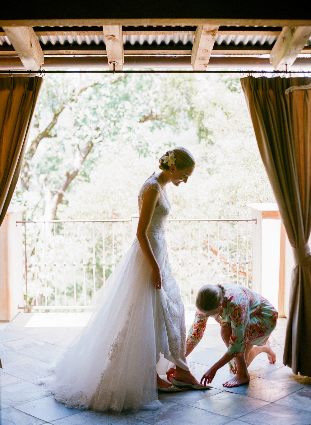 Bride steps into wedding shoes with bridesmaid; Sylvie Gil Photography