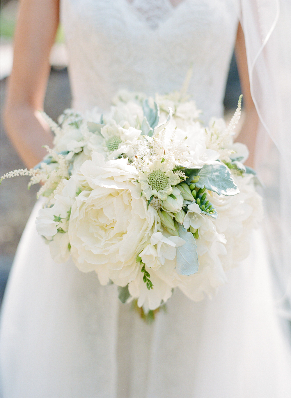 Bride holds white and green peony bouquet; Sylvie Gil Photography