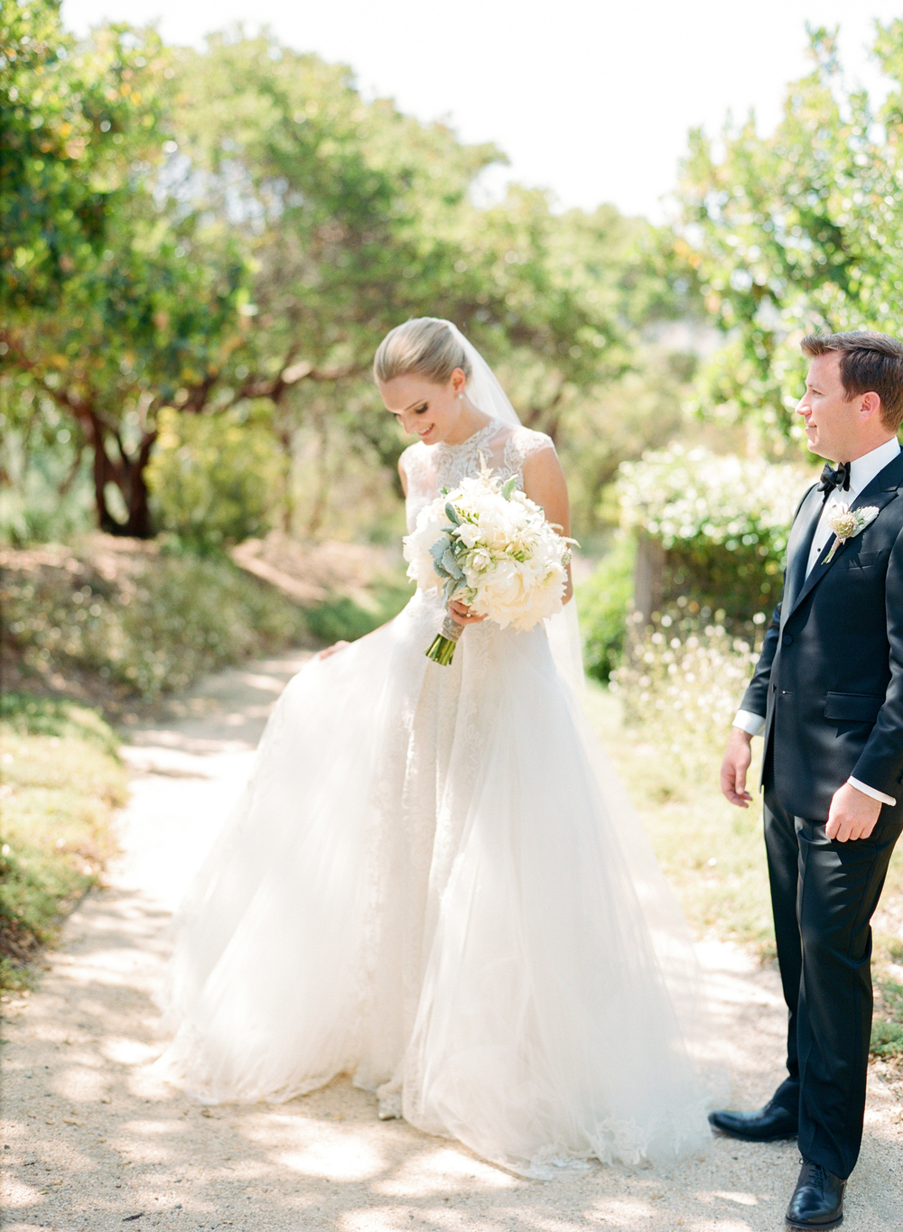 Bride stands with groom, admires her Monique Lhuillier gown; Sylvie Gil Photography