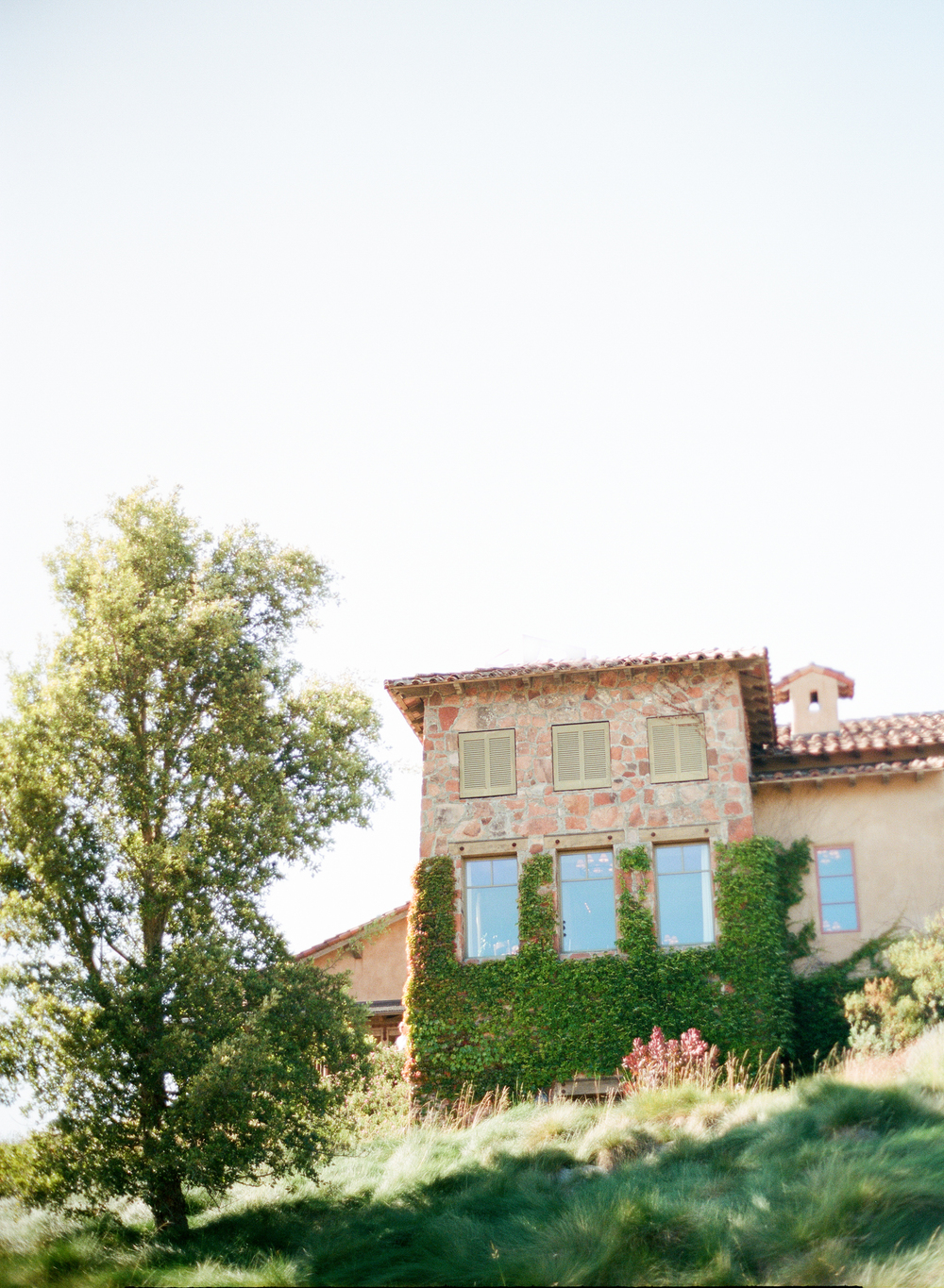 Tuscan winery building overlooking ceremony area in Calistoga Ranch; Sylvie Gil Photography