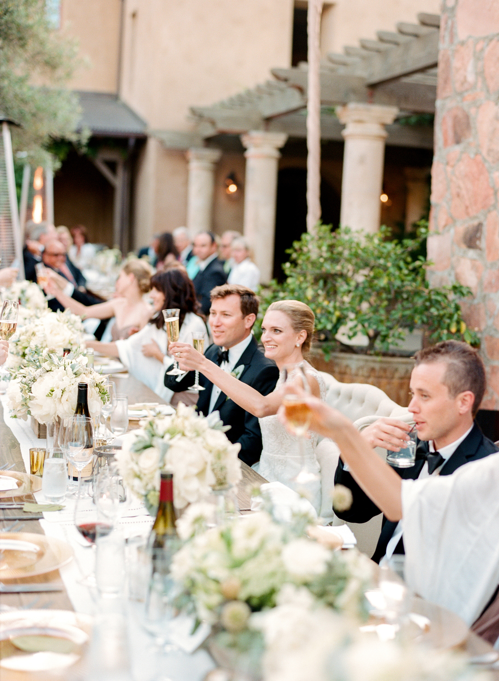 Bride and groom toast champagne at the outdoor reception in Calistoga Ranch; Sylvie Gil Photography