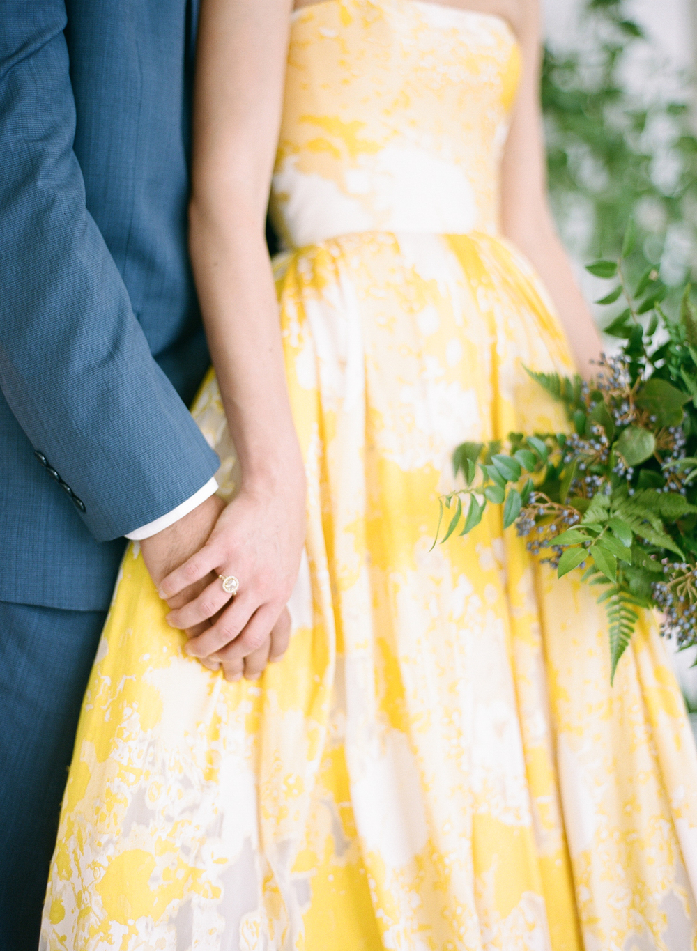 Bride and groom holding hands with vintage ring, fern bouquet; Sylvie Gil Photography