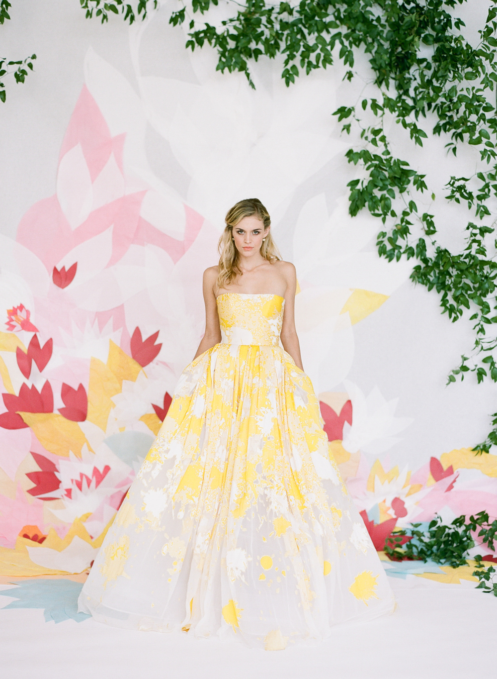 Splashy yellow strapless wedding gown, tissue paper floral backdrop; Sylvie Gil Photography