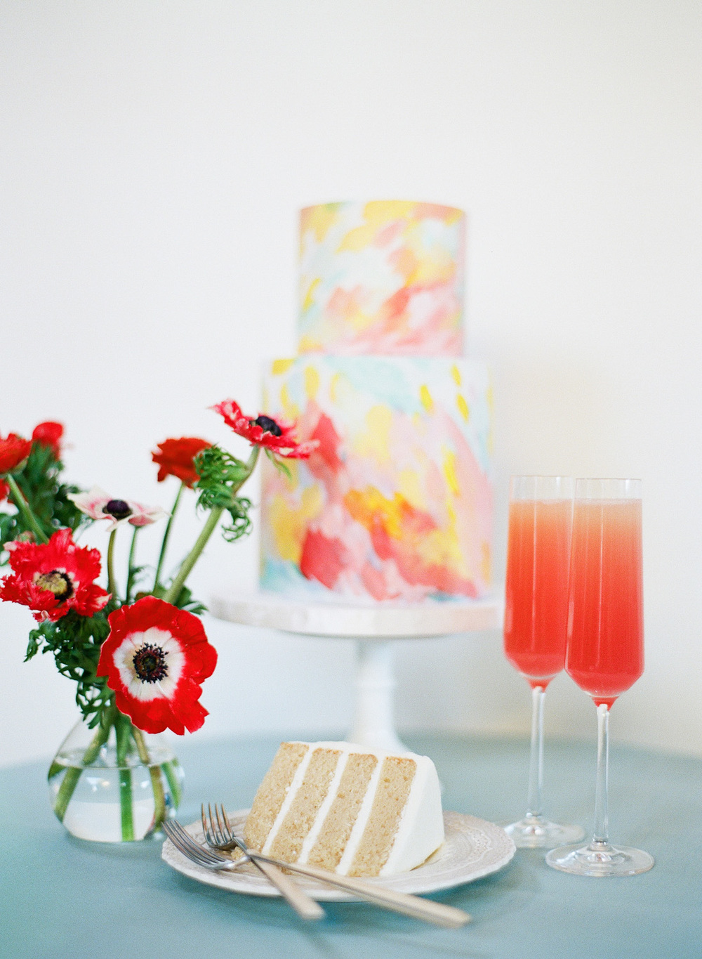 Vibrant abstract watercolors decorate a two-tier wedding cake next to grapefruit mimosas; Sylvie Gil Photography